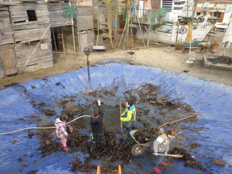 Kinder reinigen den selbstangelegten Pool