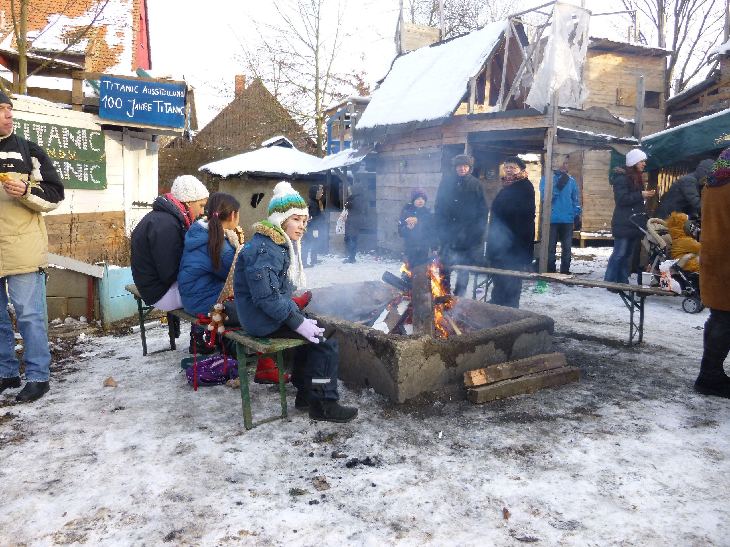 Kinder sitzen im Winter um das Lagerfeuer