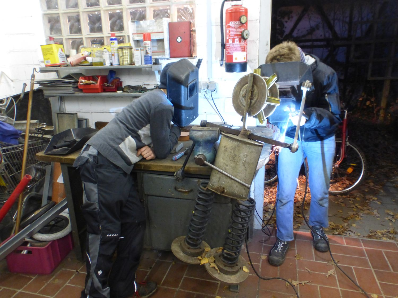 Zwei Jungs schweißen an einer Roboterfigur