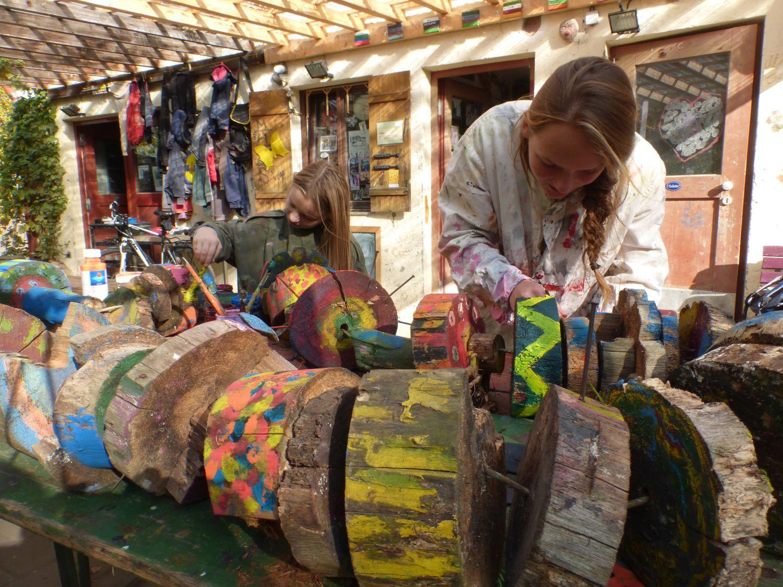 Kinder arbeiten an einer Baumskulptur
