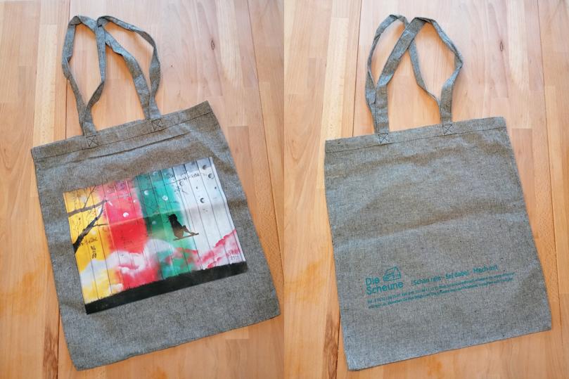 """Graue Stofftasche: Ansicht Vorderseite, bunt bedruckt; Ansicht Rückseite mit Logo und Schriftzug """"Bürgertreff Die Scheune"""""""