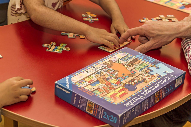 Junge und ältere Menschen spielen ein Puzzle