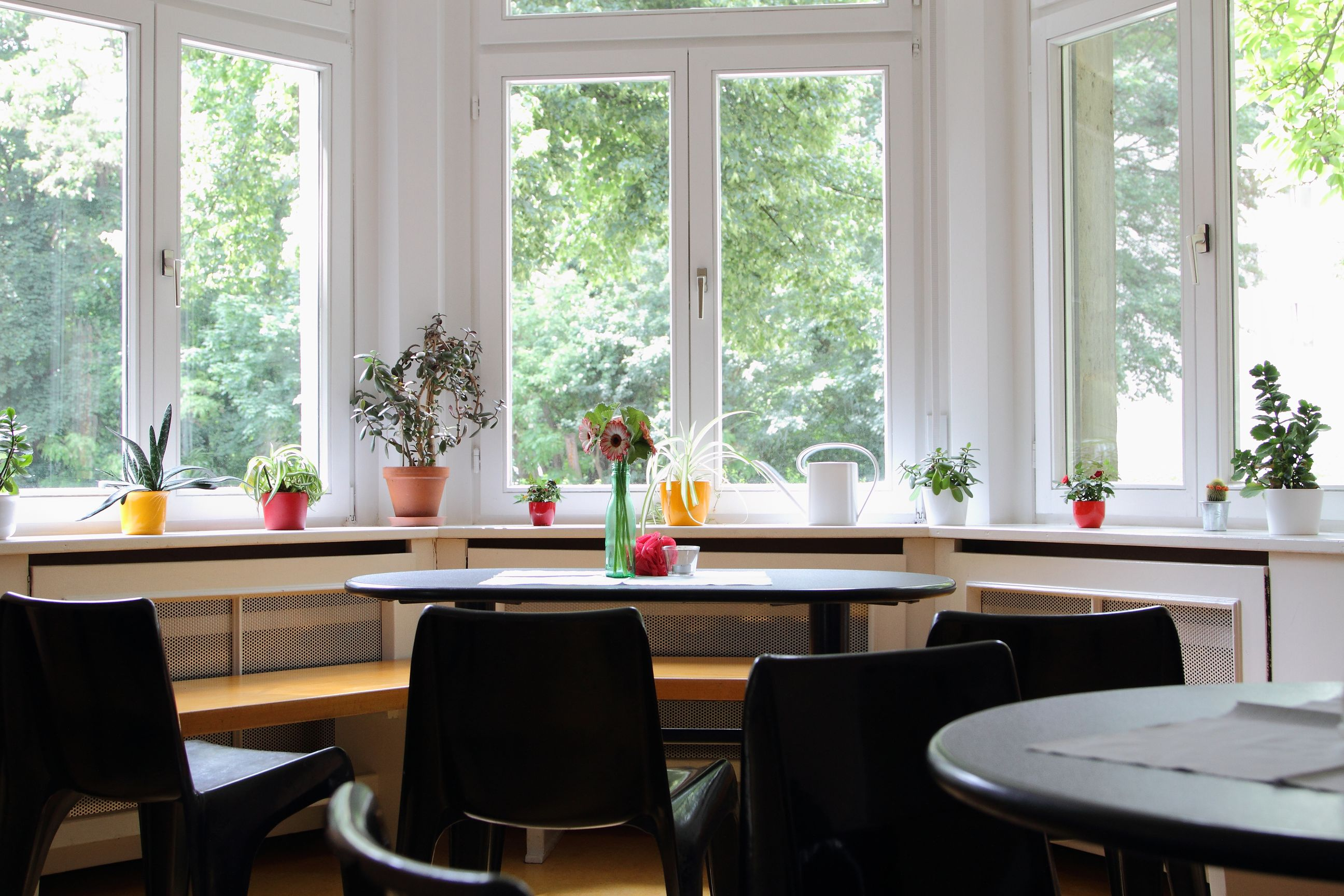 Mehrzweckbereich mit Stühlen, Tischen und Fensterfront