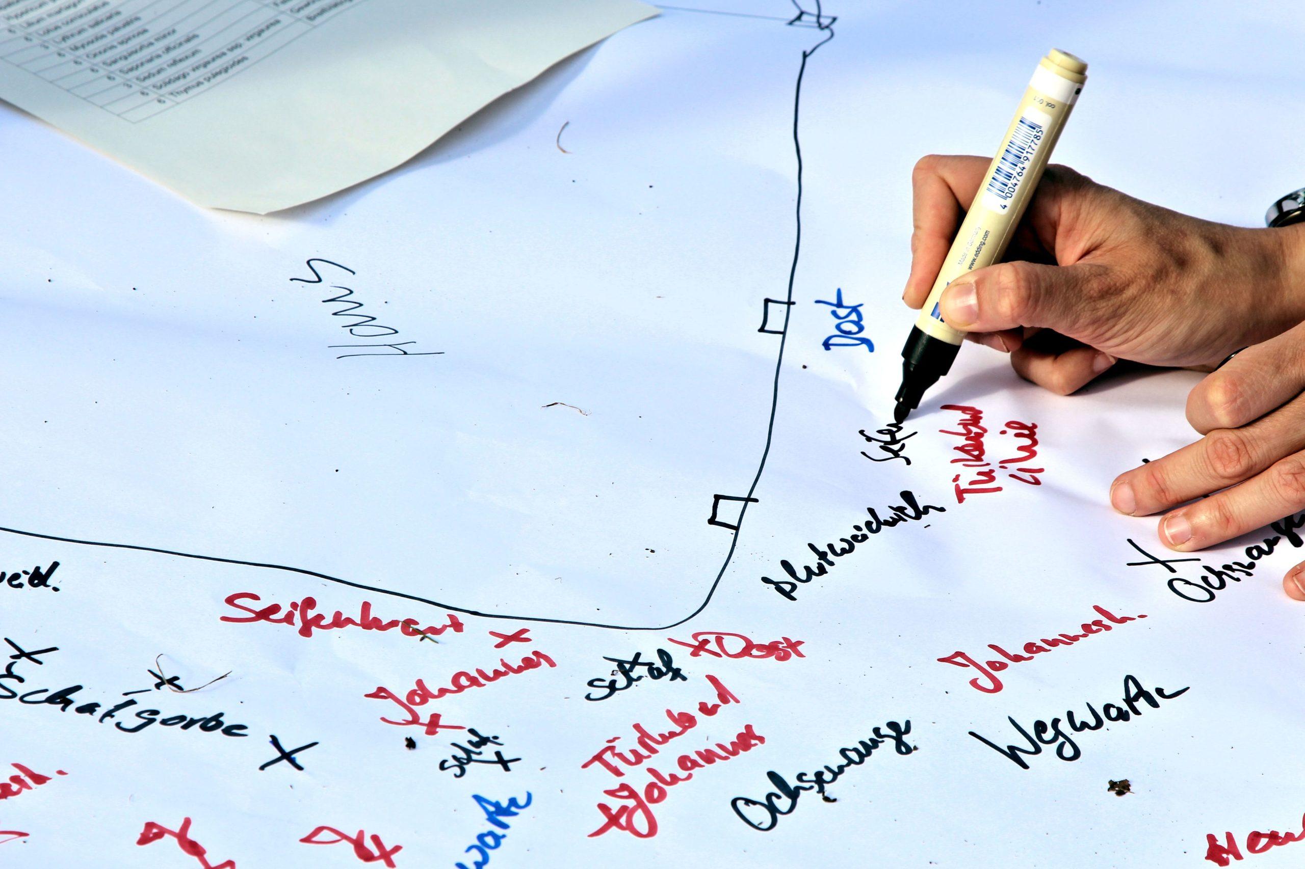 Jemand schreibt mit Filzstift auf Papier