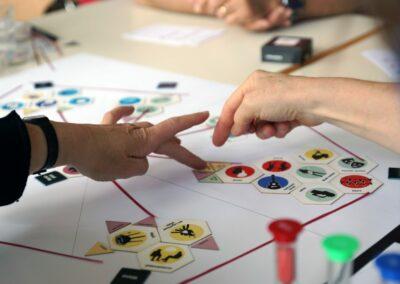 Hände verschieben auf einem Spielplan die gewünschten Funktionalitäten