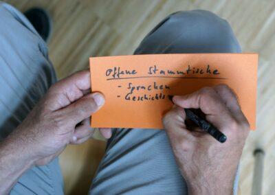 Ein Teilnehmer formuliert Ideen auf einer Karte