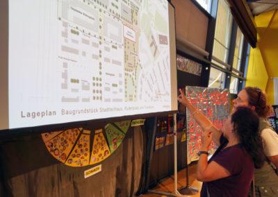 Architektin Barbara Rößner diskutiert den Bauplan mit einer Bürgerin
