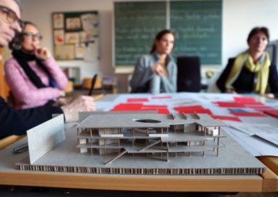 Im Vordergrund ein Pappmodell der ersten Architekturvorschläge, im Hintergrund sitzen Menschen an Tisch und blicken auf Modell.