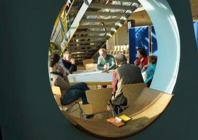 Sechs Personen sitzen um Tisch und diskutieren einen Teil der Planskizzen