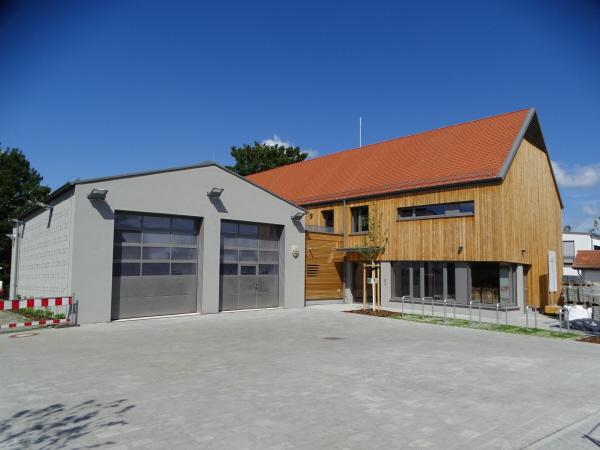 Außenansicht Bürgerhaus: Helle Holzfassade und große Feuerwehrgarage