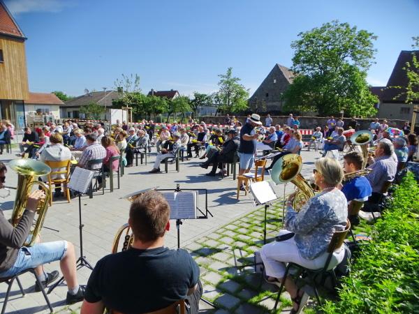 Menschen sitzen auf dem Vorplatz zum Gottesdienst versammelt, zum Teil mit Insturmenten und Notenständern