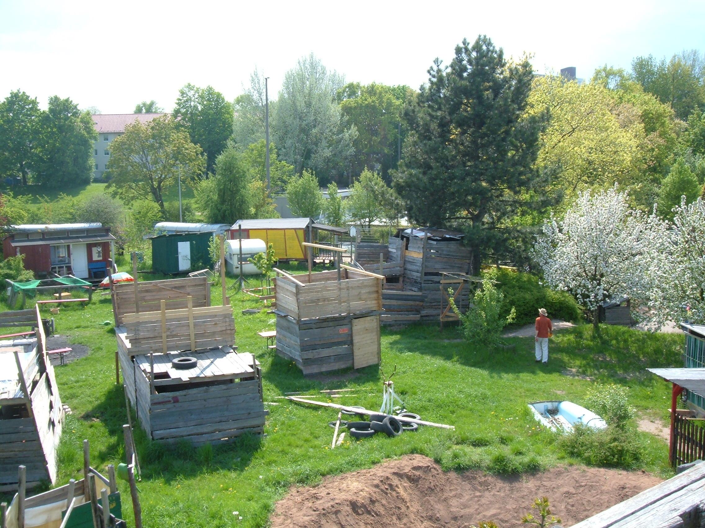 Blühender Garten mit mehreren selbstgebauten Holzhütten und Bauwägen