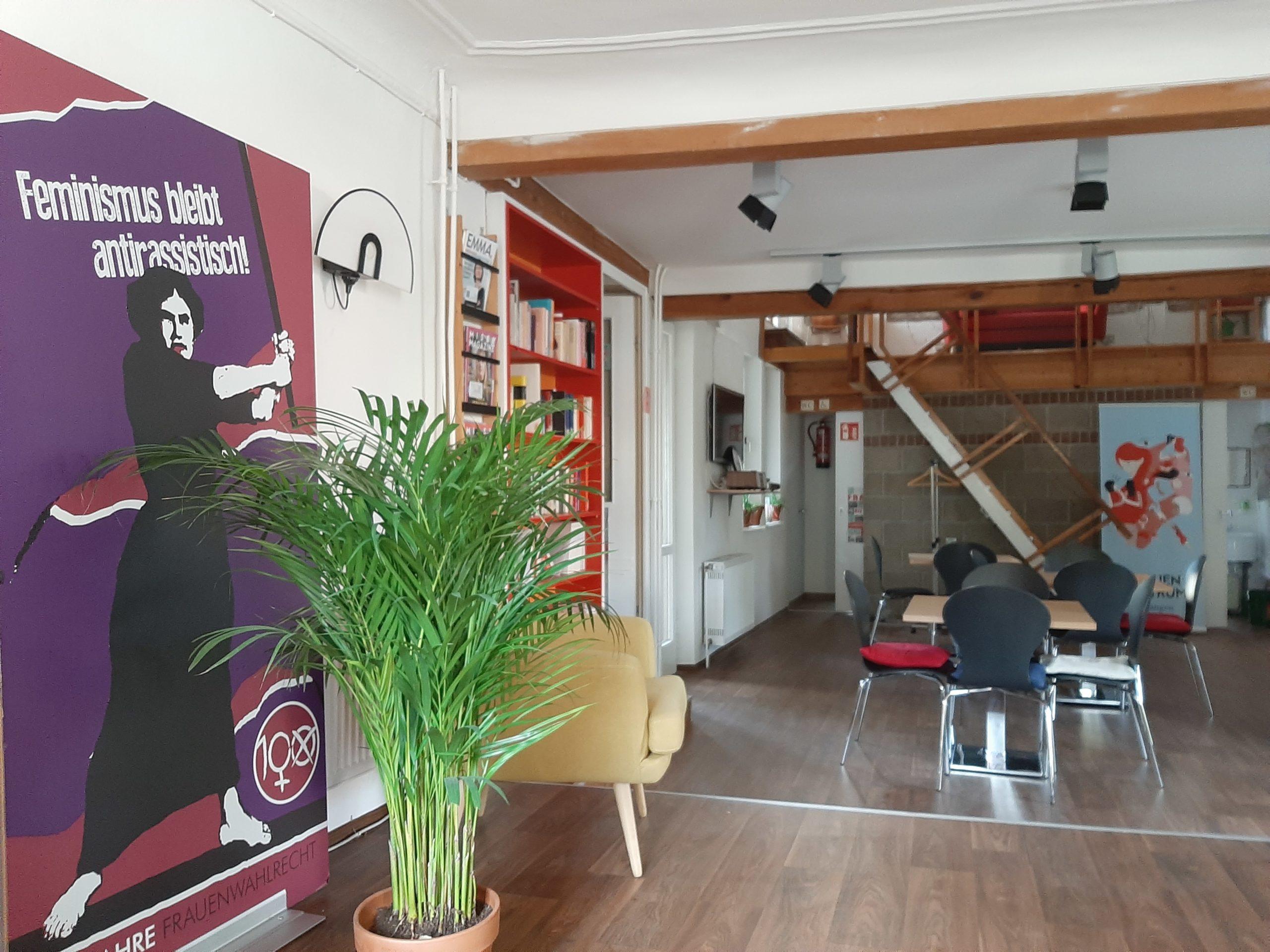 Gemütlicher Innenraum mit Büchern, Zeitschriften und Sitzgelegenheiten sowie großes Poster zum Frauenwahlrecht